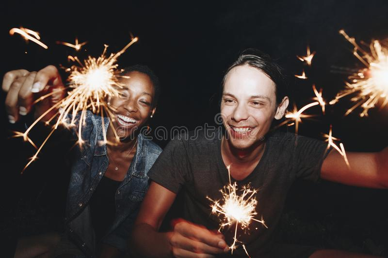 Couple playing fire sparkles in the dark royalty free stock images