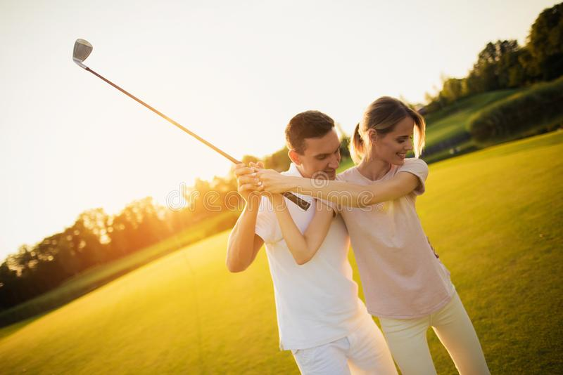Couple playing golf together at sunset, swinging together to hit the ball with a golf club stock photo