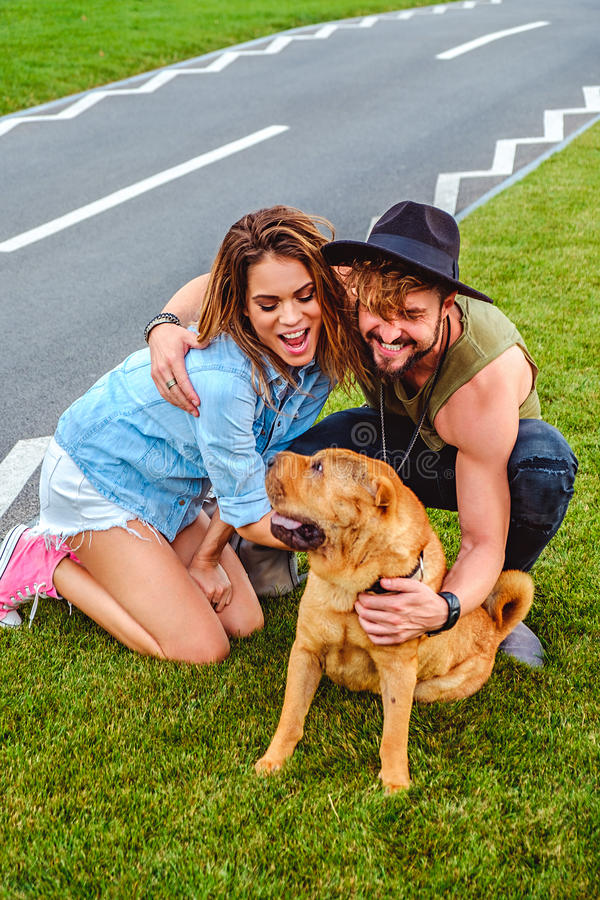 Couple playing with shar pei on the grass royalty free stock photos