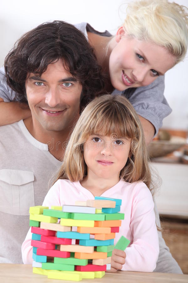 Couple playing a stacking game. With their daughter royalty free stock photo