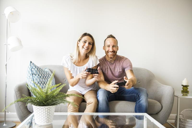 Couple playing video games at home, sitting on sofa royalty free stock photography