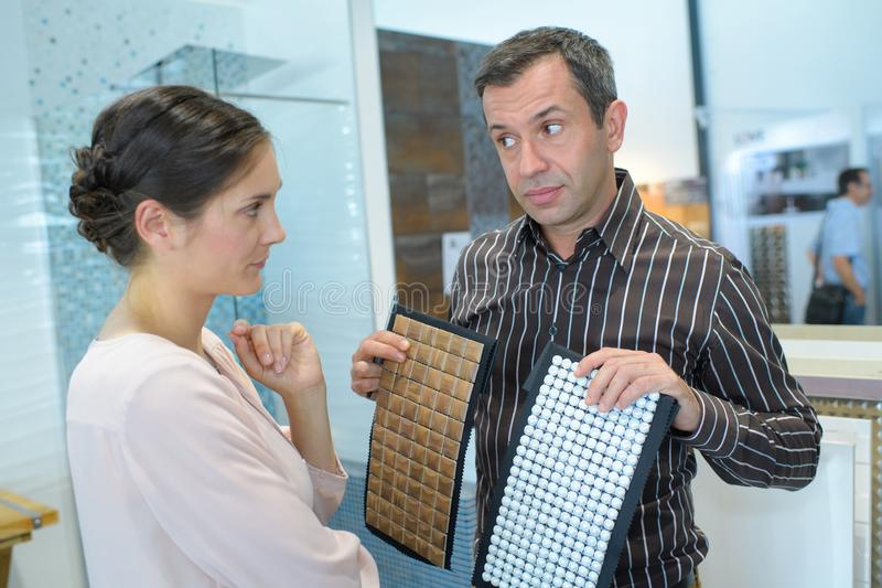 Couple pointing at ceramic mosaic tile for bathroom royalty free stock photography