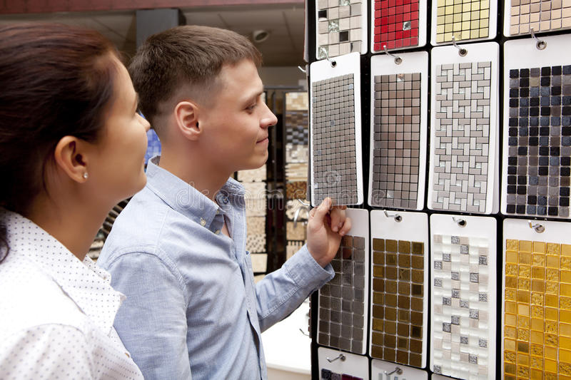Couple pointing at ceramic mosaic tile for bathroom wall in store. In home improvement warehouse exterior stock photos