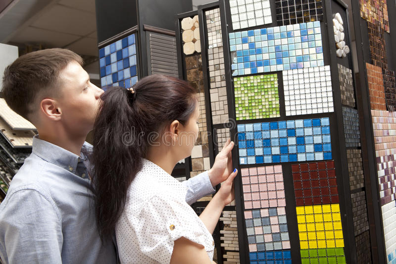 Couple pointing at ceramic mosaic tile for bathroom wall in store. In home improvement warehouse exterior royalty free stock photo