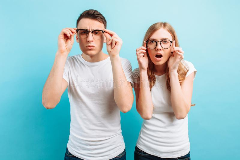 Couple with poor eyesight a man and a woman with glasses are looking into the camera trying to see something, on a blue background stock image