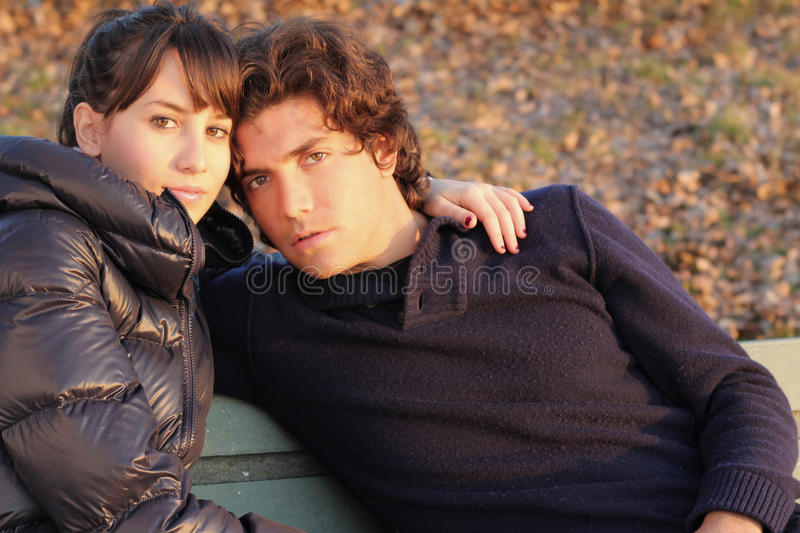 Couple portrait. Portrait of a couple hugged on a bench at sunset royalty free stock photography