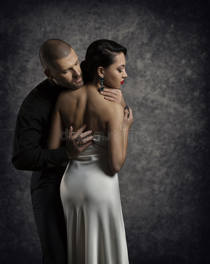 Couple Portrait, Man Woman in Love, Boy Embracing Elegant Girl. Couple Portrait, Man Woman in Love, Boy in Dark Embracing Elegant Girl in Gown with Naked Back royalty free stock photos