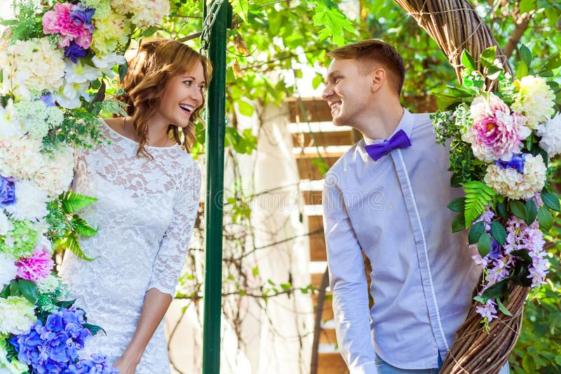 Couple posing in an arch of flowers, looking each other. Outdoor shot, spring park or summer concept. Love, sensual people royalty free stock photo