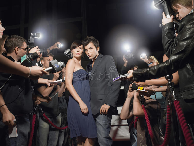 Couple Posing In Front Of Paparazzi. Young couple posing on red carpet being photographed by paparazzi stock photography