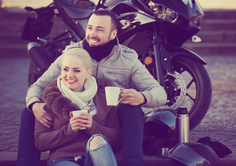 Couple posing near motor bike. Young couple posing near motor bike with sandwitches and coffee and smiling stock photography