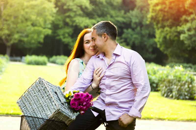 Couple posing outdoor with picnic basket and roses stock image