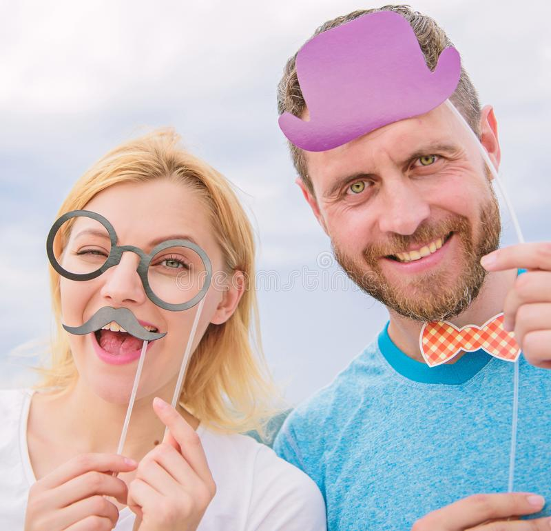 Couple posing with party props sky background. Humor and laugh concept. Photo booth props. Man with beard and woman. Couple posing with party props sky stock photo