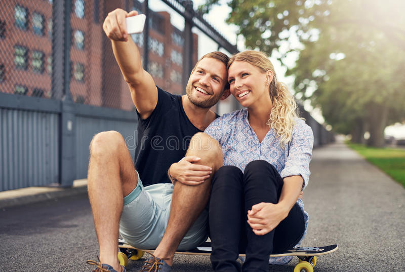 Couple posing for a selfie on a skateboard royalty free stock images