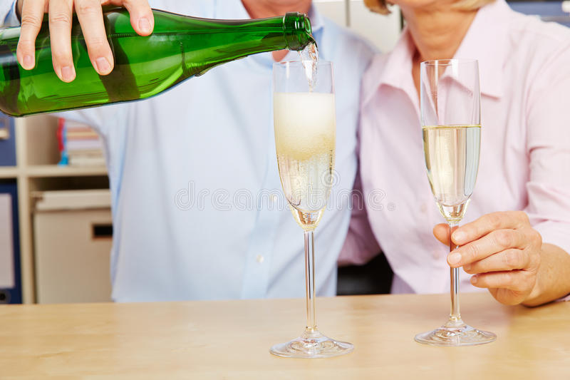 Couple pouring champagne in glass royalty free stock photography
