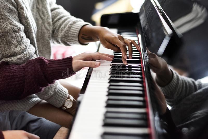 Couple practicing on a piano together stock photo