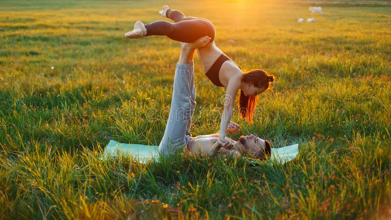 Couple practicing yoga at sunset. royalty free stock photo