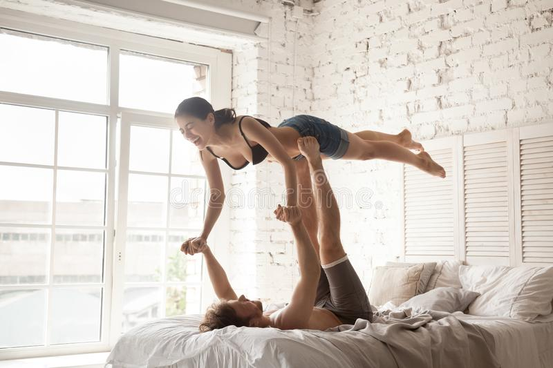 Couple practise together acro yoga at home. Cheerful millennial young married couple in love acroyogis practise acro yoga in bed at home. Sporty strong men royalty free stock photo