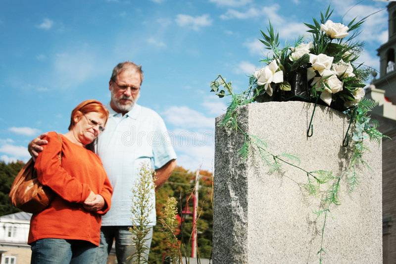 Couple praying. In front of flowered tomb, in a cemetery