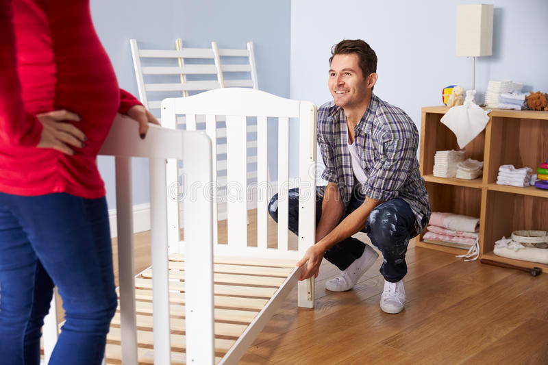 Couple With Pregnant Wife Assembling Cot In Nursery royalty free stock photography