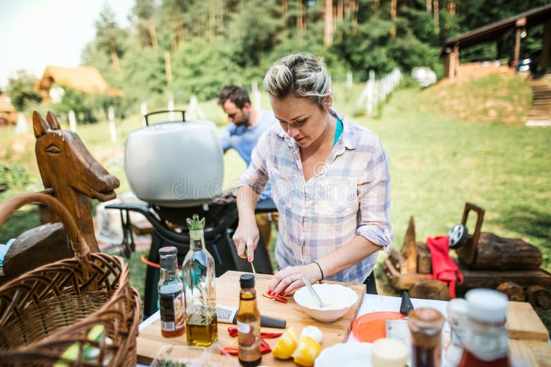 A couple preparing food on a barbecue grill in the backyard. A garden party stock photo