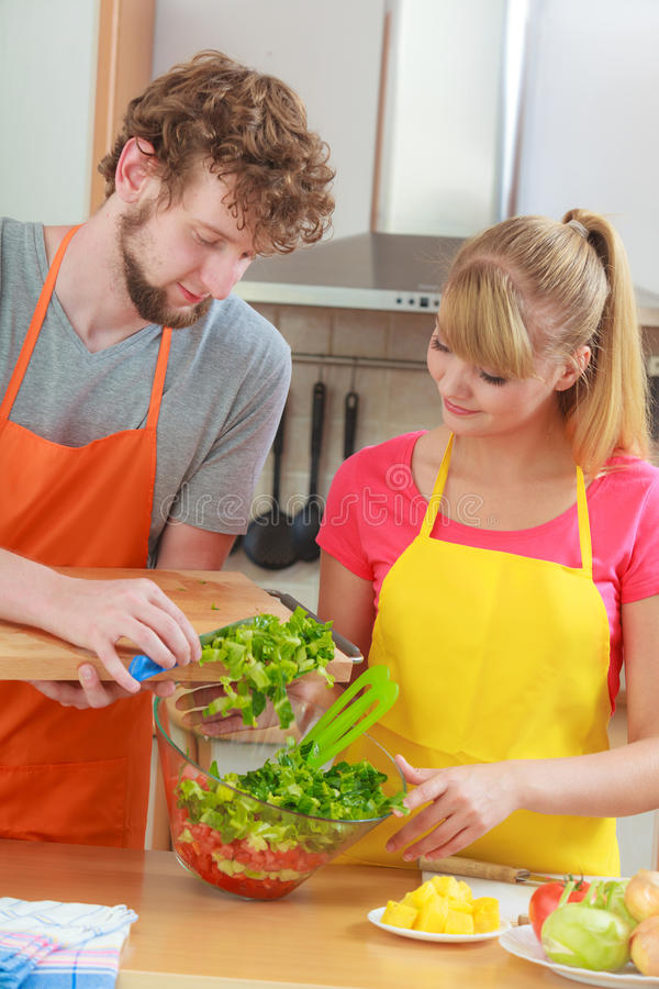 Couple preparing fresh vegetables food salad. Healthy eating, vegetarian food, cooking, dieting and people concept. Couple in kitchen at home preparing fresh stock photography