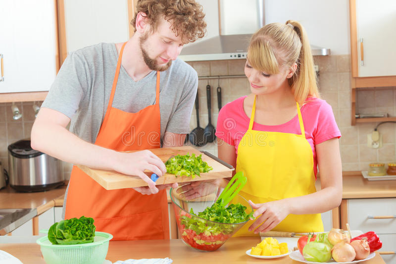 Couple preparing fresh vegetables food salad. Healthy eating, vegetarian food, cooking, dieting and people concept. Couple in kitchen at home preparing fresh royalty free stock image
