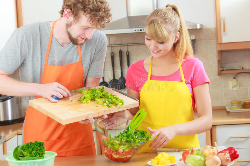 Couple preparing fresh vegetables food salad. Healthy eating, vegetarian food, cooking, dieting and people concept. Couple in kitchen at home preparing fresh stock photo