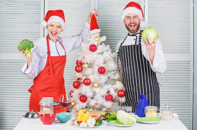 Couple preparing healthy meal together for christmas dinner. Cooking christmas meal. Man and woman chef apron santa hat. Couple preparing healthy meal together stock image