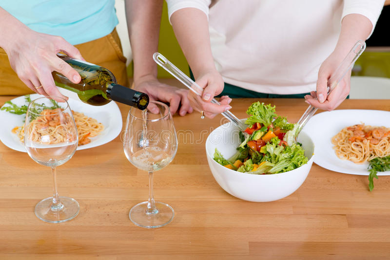 Couple preparing salad and macaroni with wine for dinner at th k stock images