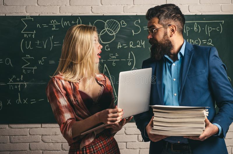 Couple of pretty sexy girl student holding heap of books and handsome bearded man teacher or professor on classroom stock images