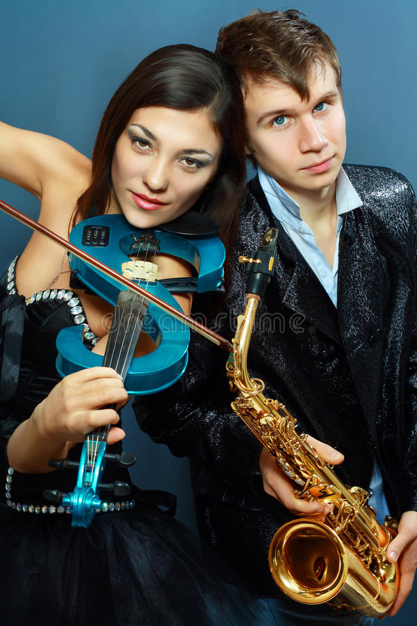 Couple of professional musicians. In modern style posing in costumes at studio royalty free stock photos