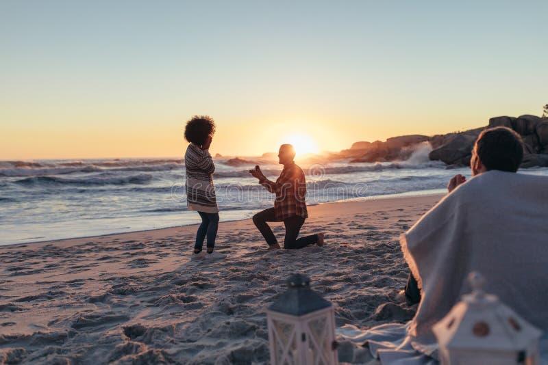 Couple proposing at beach sunset stock photo