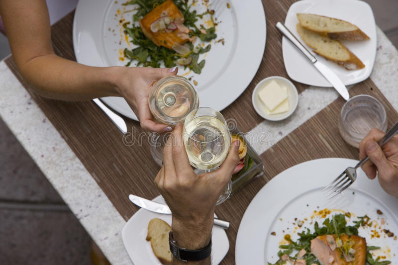Couple proposing toast with wine glasses at dinner table, elevated view royalty free stock photos