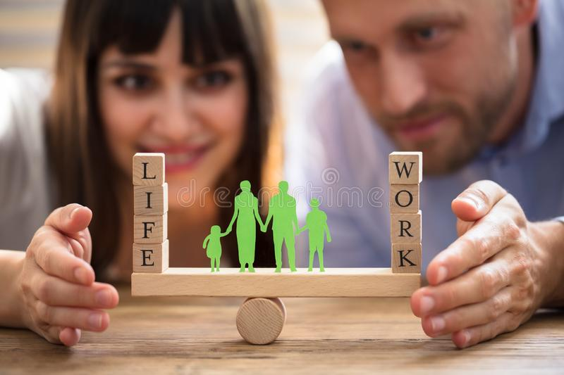 Couple Protecting Balance Between Work And Life On Seesaw royalty free stock photography