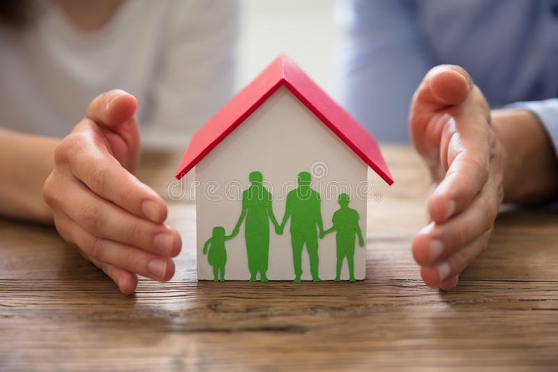 Couple Protecting Family Paper Cut Out And House Model. Couple`s Hand Protecting Family Paper Cut Out And House Model Over Wooden Desk stock photo