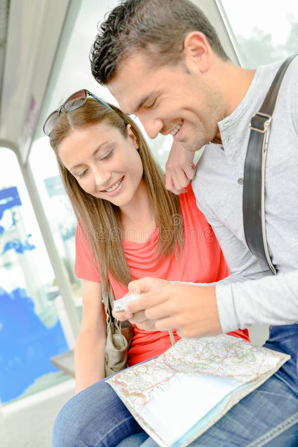 Couple on public transport looking at photos on digital camera royalty free stock photo
