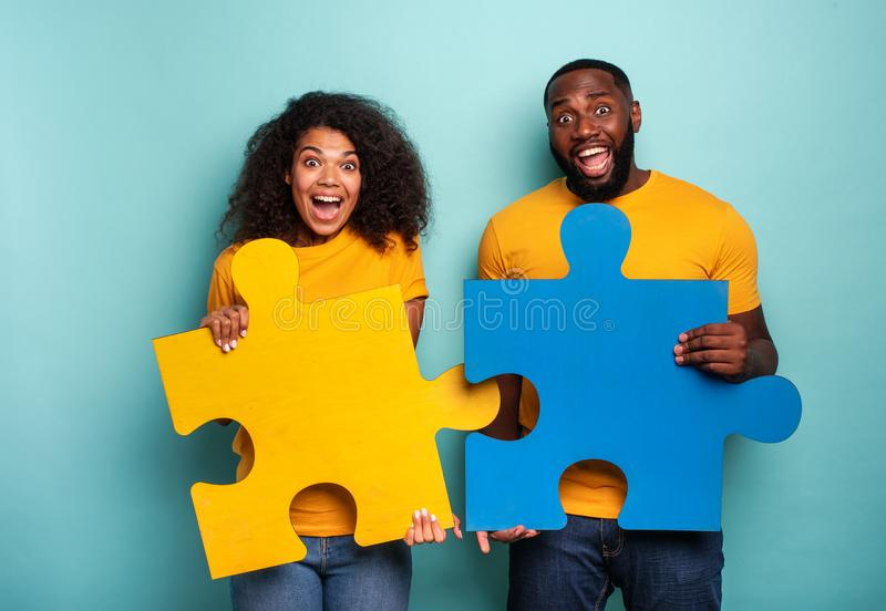 Couple with puzzles in hand over light blue background. Concept of integration, union and partnership stock photo