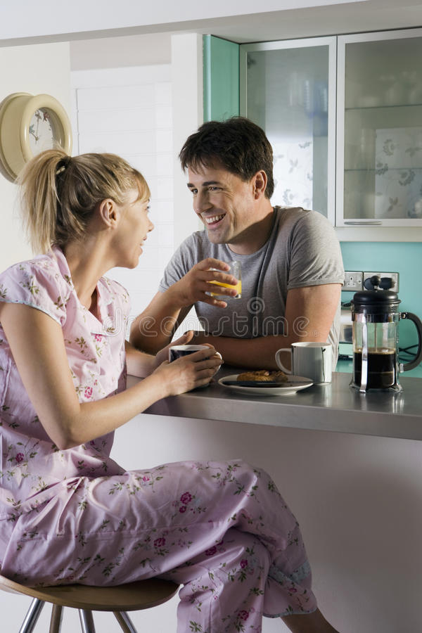 Couple in pyjamas sitting at breakfast bar in kitchen, man holding glass, woman on stool, smiling royalty free stock images