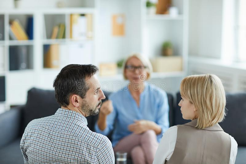 Couple in quarrel. Rear view of young displeased husband and wife looking at one another while visiting counselor royalty free stock photography