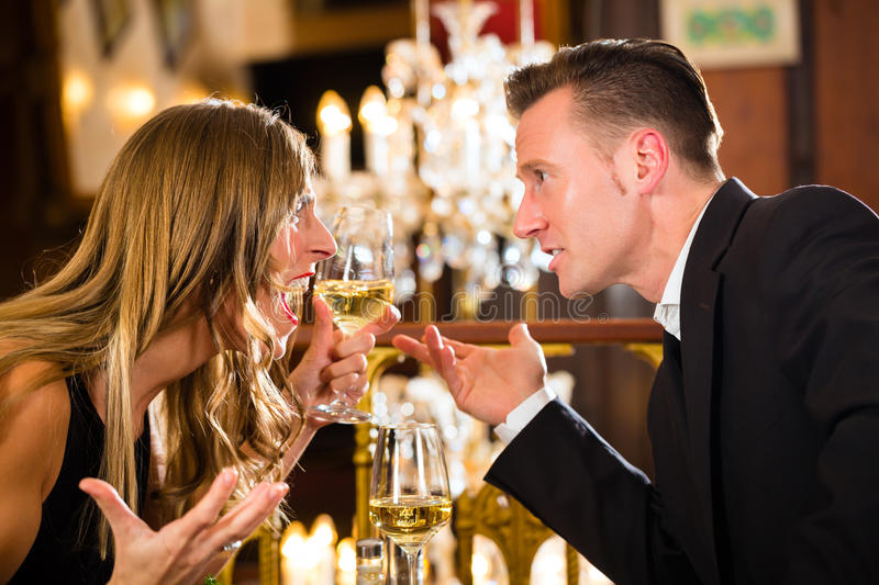 Couple quarrels at restaurant. Couple have a quarrel on a romantic date in a fine dining restaurant they are angry and yelling, a large chandelier is in stock images