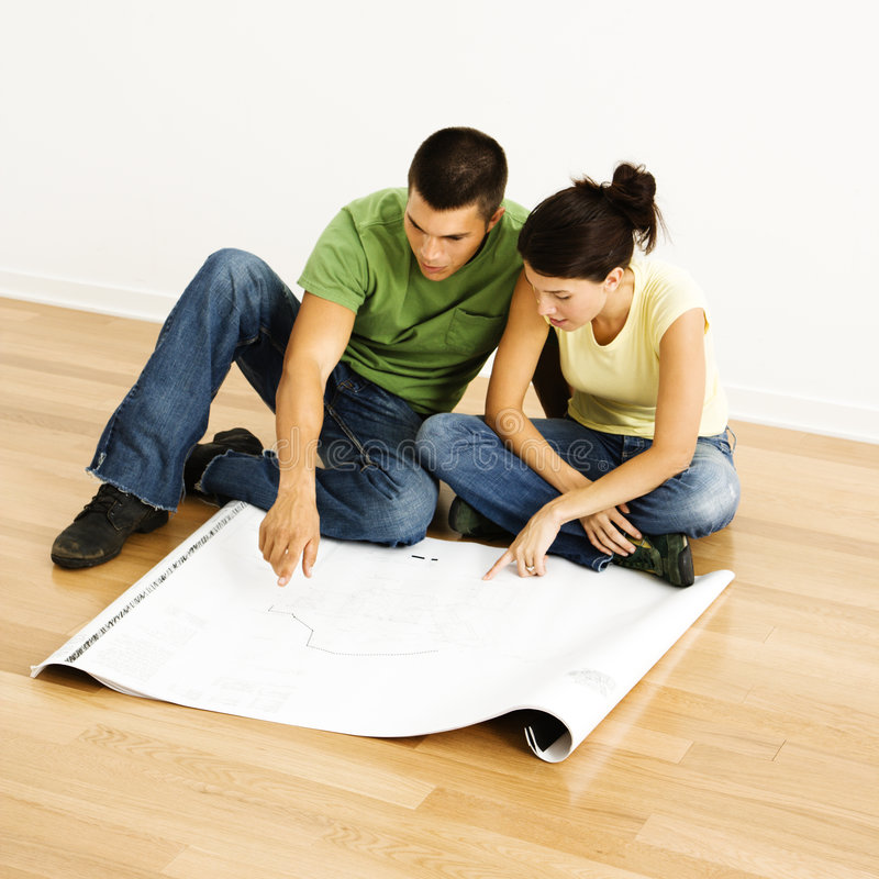 Couple reading blueprints. Attractive young adult couple looking at house plans stock image