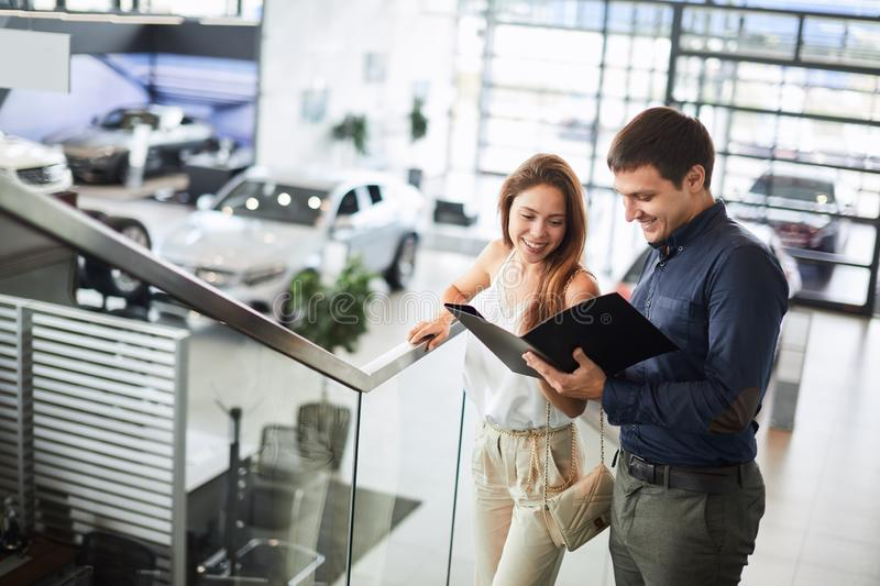 Couple reading car documentation in showroom. Attractive young couple of european appearance reading a booklet at the dealership showroom choosing a car royalty free stock photography