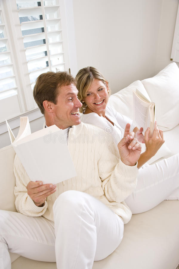 Couple reading and conversing together on sofa royalty free stock photos
