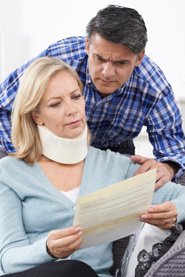Couple Reading Letter About Wife's Injury royalty free stock photography