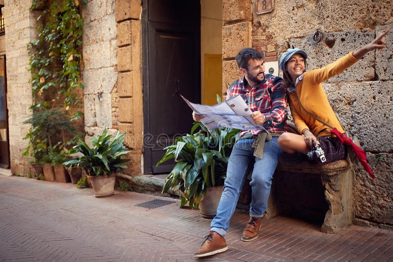 Couple reading map - young couple on travel vacation in Europe. Happy women and men in love traveling together. Couple reading map - Happy young couple on travel royalty free stock photo