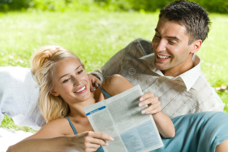 Couple reading newspaper. Couple reading together newspaper, outdoors royalty free stock photography