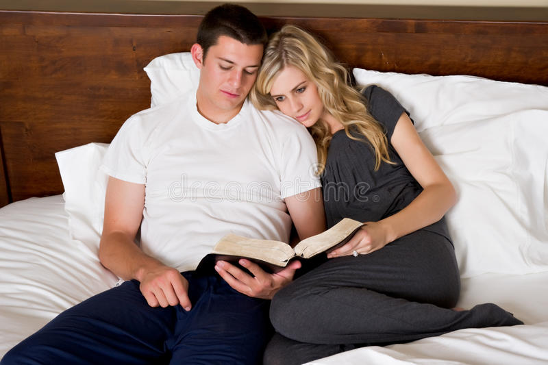 Couple reads the Bible in bed royalty free stock photography