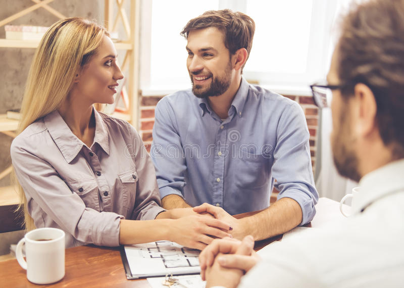 Couple and a realtor. Beautiful couple is talking with handsome realtor in suit and smiling royalty free stock image