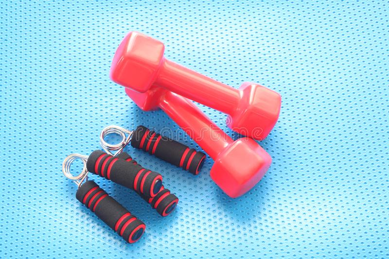 Couple of red fitness dumbbells rest on a blue gymnasium mat with copy space for your text stock image