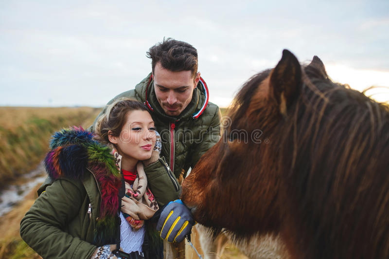 Couple and Red Horse. Couple looking at red horse in field royalty free stock photo